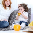 Mother gives daughter juice — Stock Photo