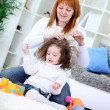 Young woman brushing her daughter's hair — Stock Photo