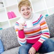 Laughing young lady sitting on sofa — Stock Photo #9774780
