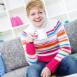 Laughing young lady sitting on sofa — Stock Photo
