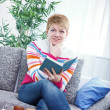 Beautiful woman reading a book on the couch — Stok fotoğraf