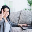 Woman with laptop showing  thumb up at home — Stock Photo