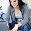 Young woman smiling while using laptop — Stock Photo