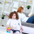 Child playing with  cubes at home with mother on sofa — Stock Photo