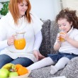 Mother and daughter drinking orange juice — Stock Photo