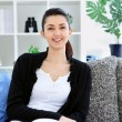 Attractive woman sitting on sofa at home, smiling — Stock Photo