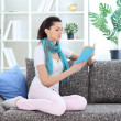 Woman reading a book in her living room — Stockfoto