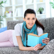 Woman holding a book in her living room — Stockfoto