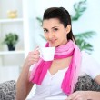 Stock Photo: Woman sitting on couch at home, drinking coffee