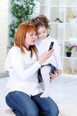 Mother and daughter using cell phone — Stock Photo