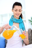 Girl pouring orange juice — Stock Photo