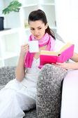 Woman sitting on sofa holding book ad drinking coffee — Stock Photo