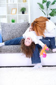 Mother playing with her daughter on couch — Stock Photo