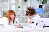 Mother and daughter writing together — Stock Photo