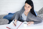 Young girl drinking tea and writing — Stock Photo
