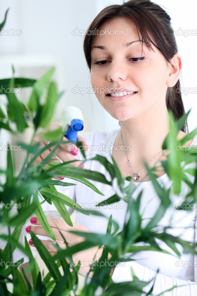 Woman taking care of flowers in her living room — Stock Photo #9774217