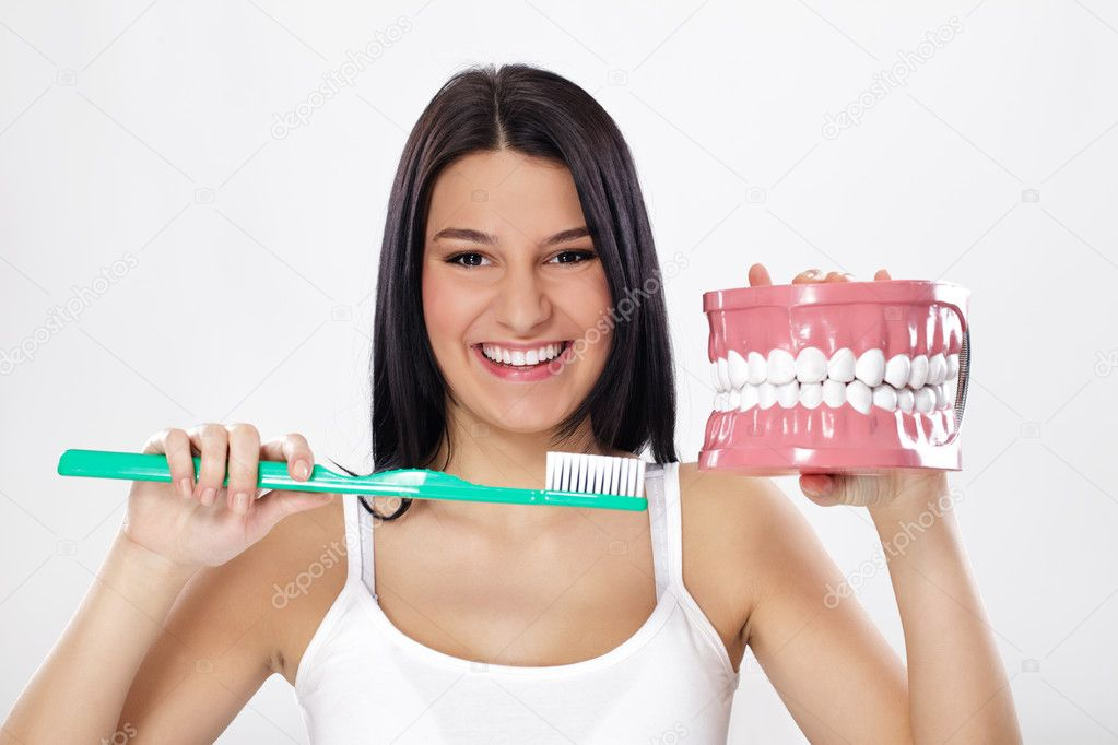 Smiling girl holding model of teeth and toothbrush — Stock Photo #9774605