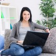 Woman relaxing and using laptop smiling — Stock Photo #9919562