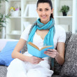 Happy young woman sitting  on couch with book — Lizenzfreies Foto