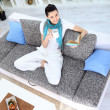 Pretty young woman relaxing on sofa at home and reading book — Stok fotoğraf