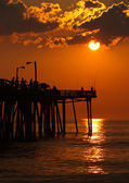 Sylwetki rybaków na wschód słońca na molo w północnej caro — Zdjęcie stockowe