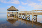 Gazebo, dock, blue sky and clouds over calm sound waters — Stock Photo