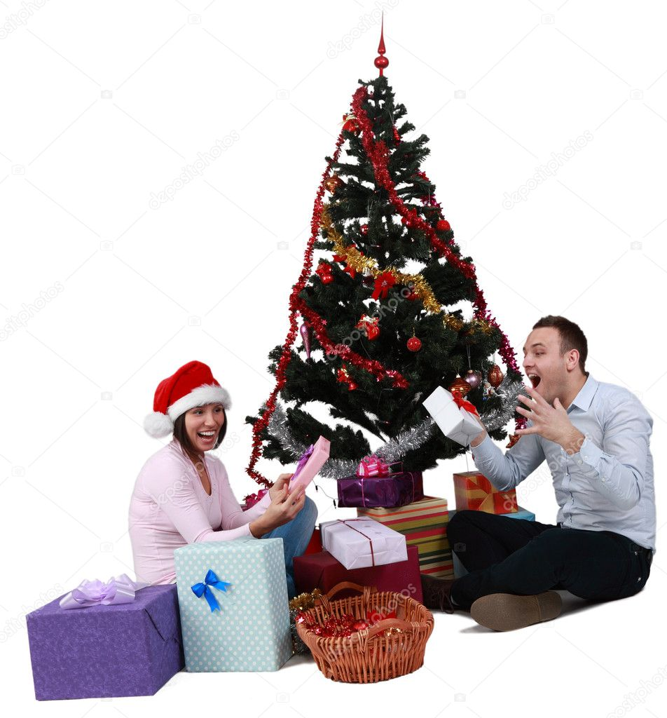 Studio shot of a young couple enjoying the gifts in front of the Christmas Tree, against a white background. — Stok fotoğraf #7972905