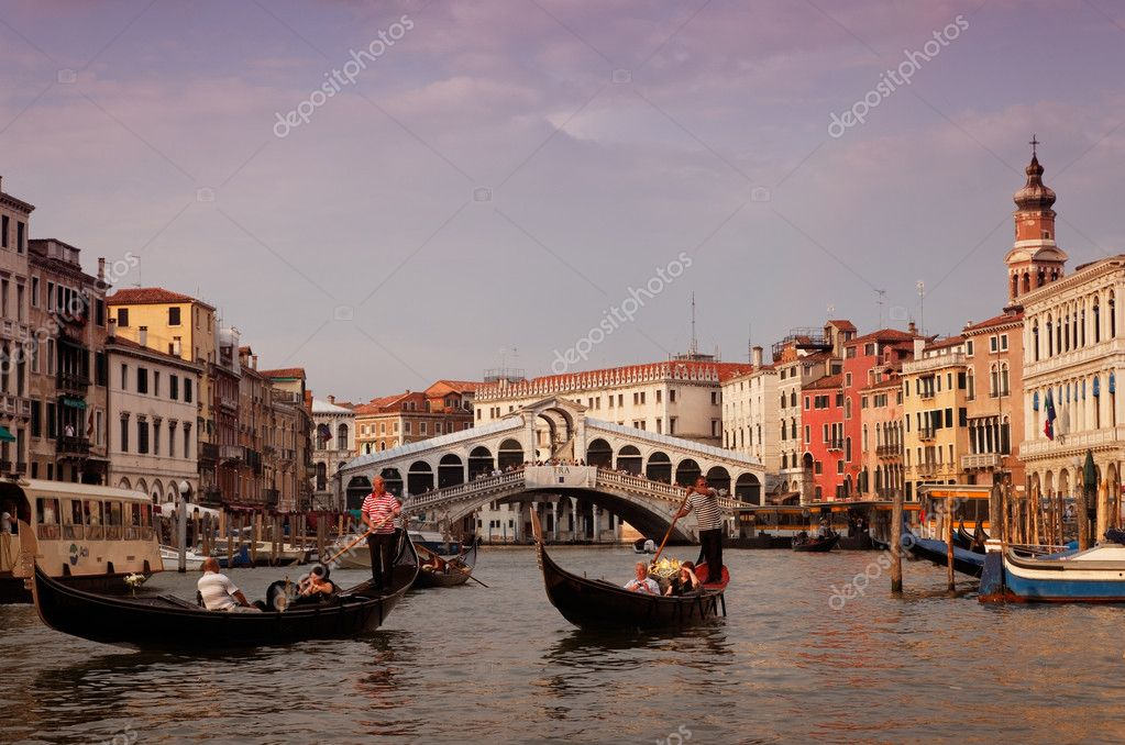 Venice,Italy,July 29th 2011: Gondoliers sailing on Grand Canal in front of the Rialto Bridge in Venice.  Stock Photo #9014691