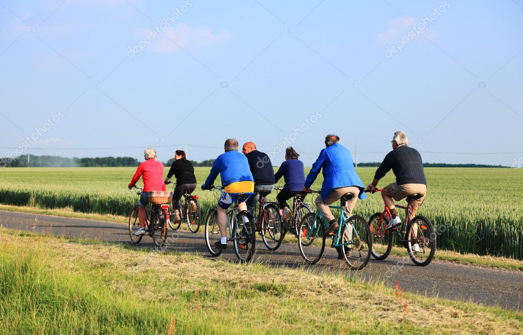 Blandainville, June 2nd 2010: A group of senior riding their bicycles on a lane between wheat fields in Centre region of France. — Stock Photo #9046432