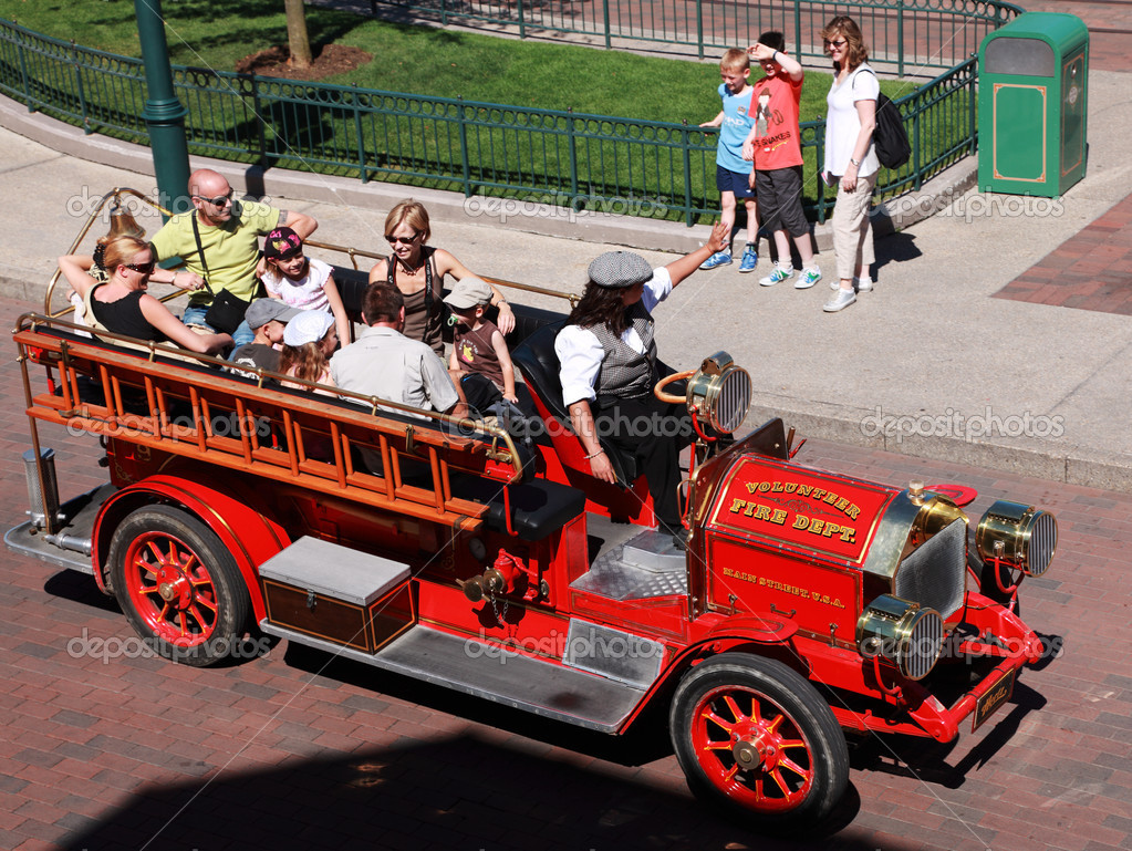 Paris,France,July 11th 2010: Upper view of an old-fashion Fire Department car transporting a group of tourists in the streets of Disneyland Park in Paris. — Stock Photo #9215532