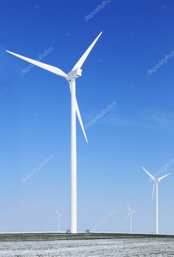 Image of a field with windturbines covered by snow in winter.  Stock Photo #9620771