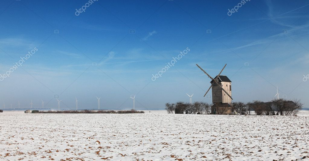 Winter landscape in the central region of France, with a traditional wooden windmill and some modern windturibines in the distance. — Stock Photo #9620778