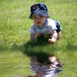 Baby in the Grass by Water — Stok fotoğraf