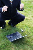 Business Man in Grass with Laptop — ストック写真