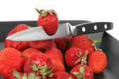 Strawberries on Black Plate over White with knife — Stock Photo