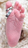 Babies foot taken closeup with rings — Stock Photo