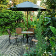 Stock Photo: Garden furniture - rattchairs and table under umbrellon w