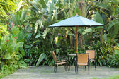 Garden furniture - rattan chairs and table under umbrella on a w — Stock Photo
