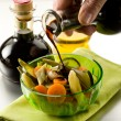 Pouring balsamic vinegar over steamed vegetables salad — Stock Photo #10064380