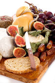 Cheeseboard with an assortment of cheeses and fruits — Stock Photo
