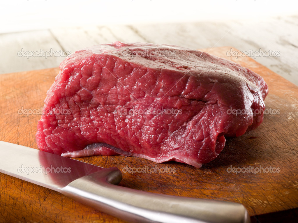 Meat with knife over cutting board  Stock Photo #9456694