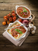 Ravioli with ragout sauce on wooden table — Stock Photo
