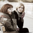 Two young women sitting on a bench - Stock Photo