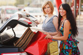 Two young shoppers on a car parking — Stock Photo