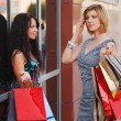 Стоковое фото: Two young women with shopping bags