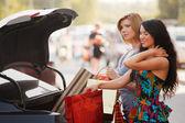Dois compradores jovens em um parque de estacionamento de carro — Foto Stock