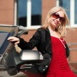 Foto Stock: Young blonde woman with a car