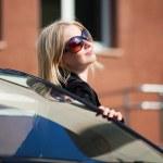 jonge blonde vrouw met een auto — Stockfoto