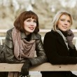 Two young women sitting on a bench — Stock Photo