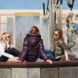 Teenage girls relaxing against a city fountain - Stok fotoğraf